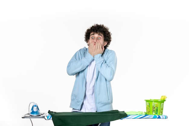 Vorderansicht junger mann hinter bügelbrett schockiert auf weißem hintergrund hausarbeit bügeln farbe wäsche kleidung reinigung emotion mann