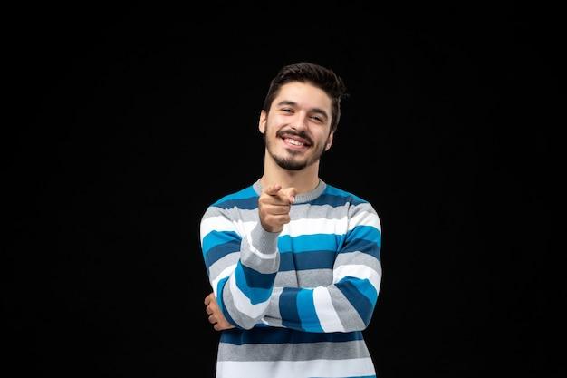 Vorderansicht junger mann im blau gestreiften trikot auf schwarzer wand