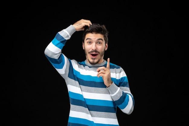 Vorderansicht junger mann im blau gestreiften trikot, das seine haare an der schwarzen wand zieht