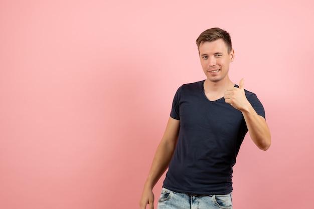 Vorderansicht junger mann im blauen t-shirt, das gerade auf rosa hintergrundmannmodell-emotionsfarbe männlich aufwirft