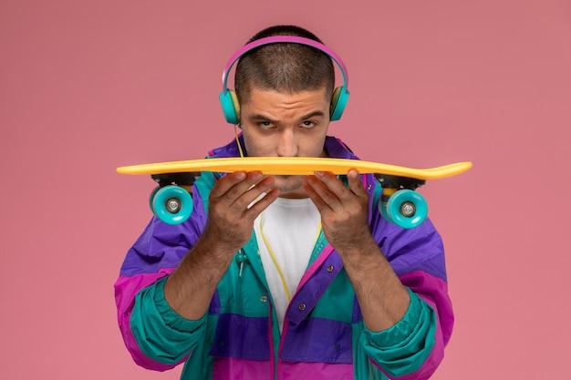 Vorderansicht junger mann im bunten mantel, der musik auf rosa schreibtisch hört