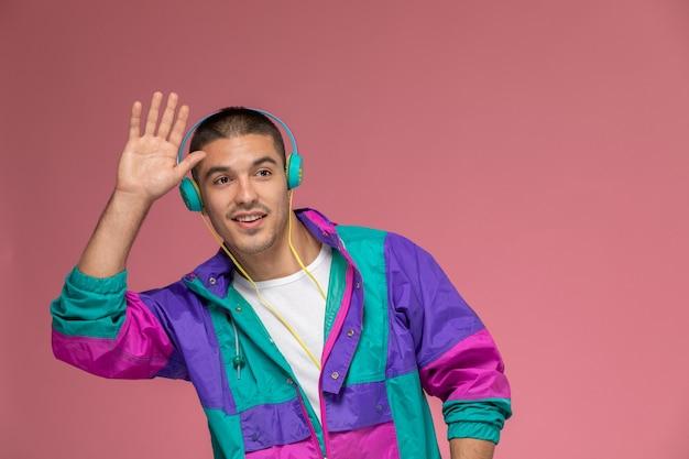 Vorderansicht junger mann im bunten mantel, der musik hört, die auf dem rosa hintergrund winkt
