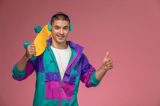 Vorderansicht junger mann im bunten mantel, der musik hört, die skateboard auf dem rosa schreibtischmann hält