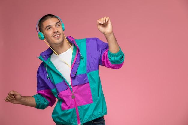 Vorderansicht junger mann im bunten mantel, der musik hört und auf dem rosa hintergrund tanzt