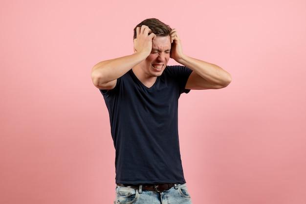 Vorderansicht junger mann im dunkelblauen hemd, das kopfschmerzen auf den männlichen menschlichen modellfarbmannemotionen des rosa hintergrunds hat