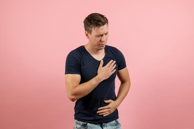 Vorderansicht junger mann im dunkelblauen hemd, das probleme mit herz auf rosa hintergrund männlicher menschlicher farbmannmodellemotionen hat