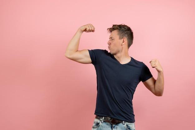 Vorderansicht junger mann im dunkelblauen t-shirt posiert und beugt sich auf rosa hintergrund