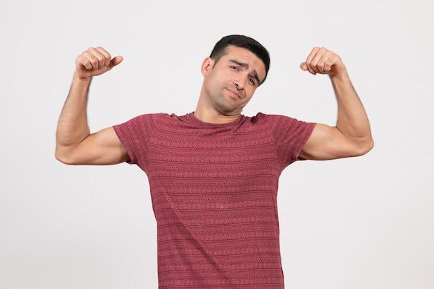 Vorderansicht junger mann im dunkelroten t-shirt, das auf weißem hintergrund steht und sich biegt