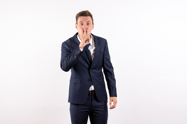 Vorderansicht junger mann im eleganten klassischen anzug bittet um stille auf weißem hintergrund