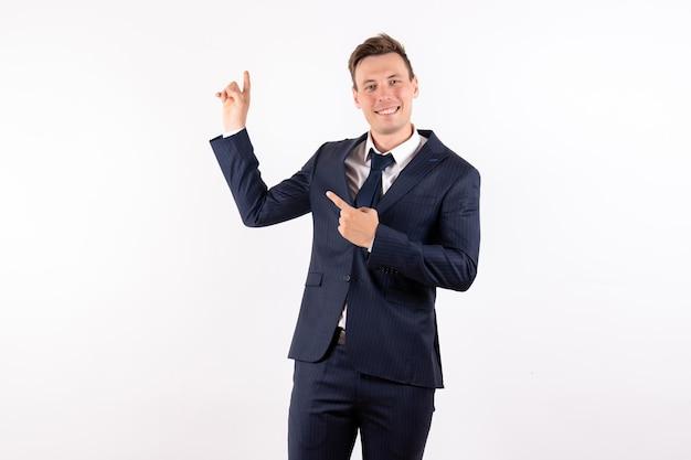 Vorderansicht junger mann im eleganten klassischen anzug lächelnd auf weißem hintergrund