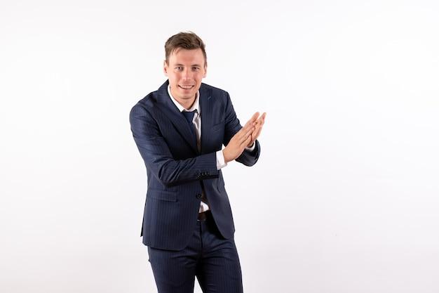 Vorderansicht junger mann im eleganten klassischen anzug lächelnd und klatschend auf weißem hintergrund