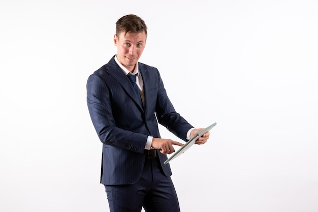 Vorderansicht junger mann im eleganten klassischen anzug mit riesigen taschenrechner auf weißem hintergrund