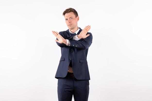 Vorderansicht junger mann im eleganten klassischen anzug mit verbotszeichen auf weißem hintergrund