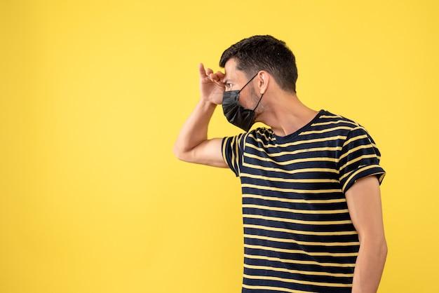 Vorderansicht junger mann im gestreiften schwarzweiss-t-shirt, das etwas auf gelbem hintergrund betrachtet