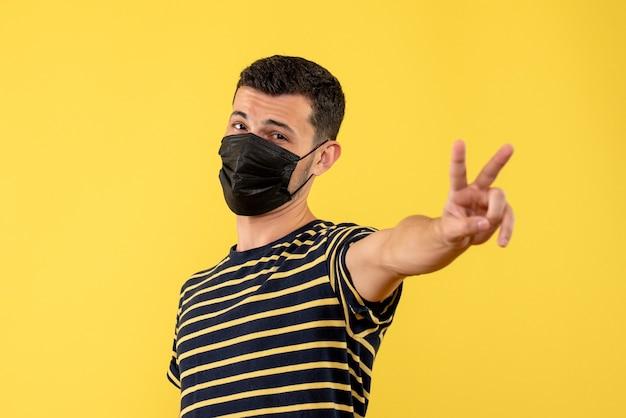 Vorderansicht junger mann im gestreiften schwarzweiss-t-shirt, das gelben hintergrund des siegeszeichens macht