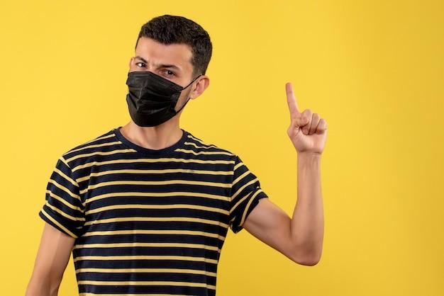 Vorderansicht junger mann im gestreiften schwarzweiss-t-shirt, das mit gelbem hintergrund des fingers oben zeigt
