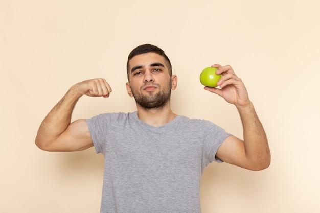 Vorderansicht junger mann im grauen t-shirt, das apfel hält und auf beige biegt
