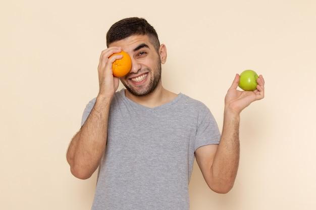 Vorderansicht junger mann im grauen t-shirt, das apfel und orange schreibtisch hält