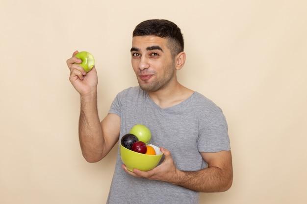 Vorderansicht junger mann im grauen t-shirt, der platte mit früchten beißt, die apfel lächeln auf beige