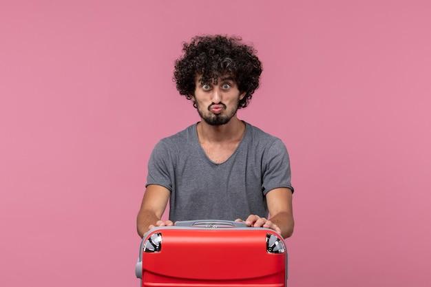 Vorderansicht junger mann im grauen t-shirt, der sich auf die reise auf dem rosa schreibtisch vorbereitet