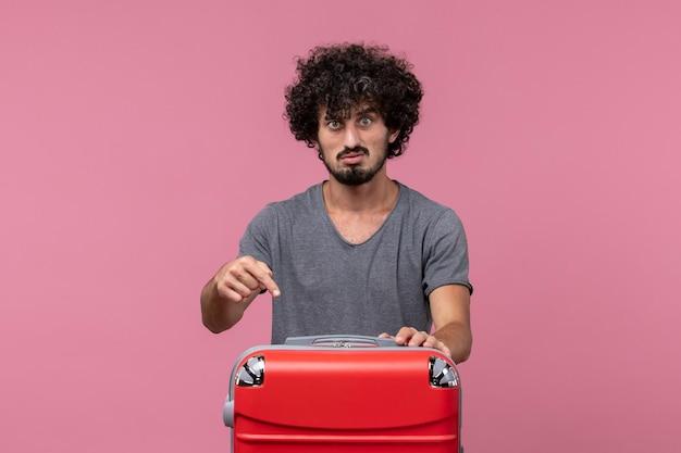 Vorderansicht junger mann im grauen t-shirt, der sich auf eine reise auf hellrosa raum vorbereitet