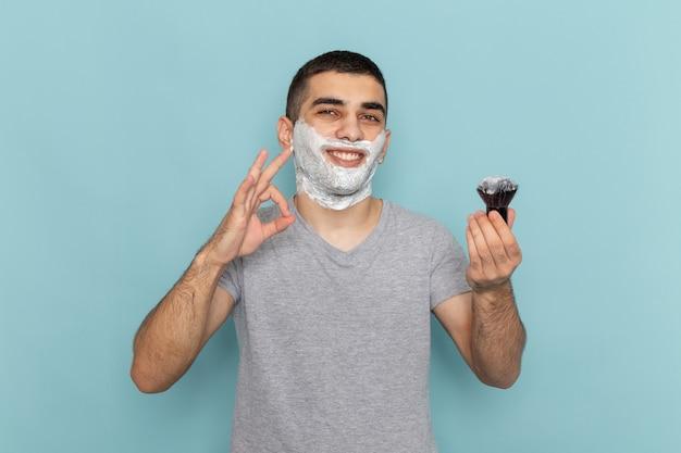 Vorderansicht junger mann im grauen t-shirt mit weißem schaum auf seinem gesicht, das auf eisblau lächelt