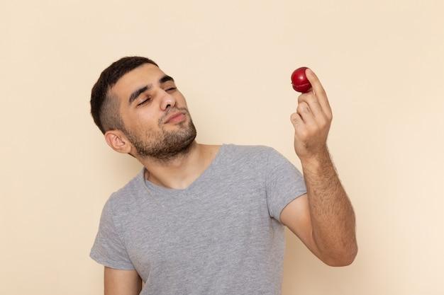 Vorderansicht junger mann im grauen t-shirt und in den blauen jeans, die saure rote pflaume auf beige halten