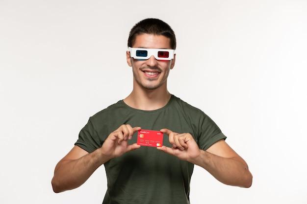 Vorderansicht junger mann im grünen t-shirt, das bankkarte in d sonnenbrille auf einsamem kino des weißen wandfilms hält