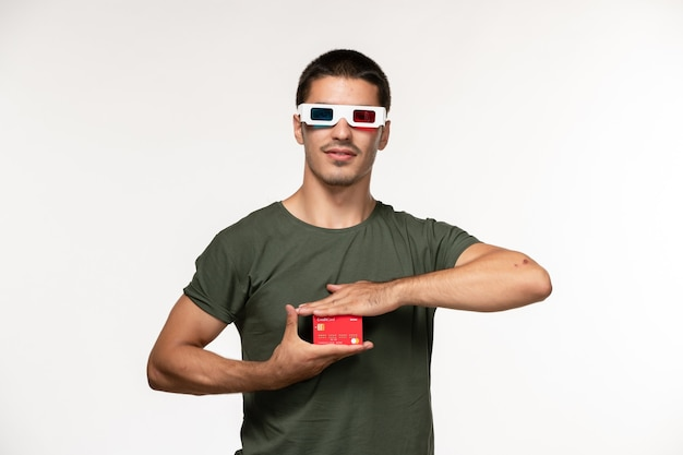 Vorderansicht junger mann im grünen t-shirt, das bankkarte in d sonnenbrille auf einsamem kinofilm der weißen wand hält