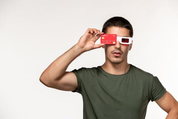 Vorderansicht junger mann im grünen t-shirt, das bankkarte in d sonnenbrille auf weißem einsamen kinofilm des weißen wandfilmmanns hält