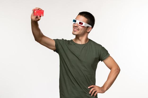 Vorderansicht junger mann im grünen t-shirt, das bankkarte in d sonnenbrille auf weißem wandfilm einsamen kinofilm hält
