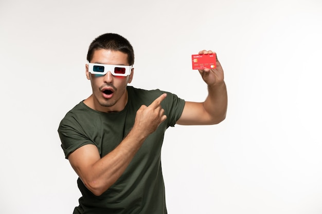 Vorderansicht junger mann im grünen t-shirt, das bankkarte in d sonnenbrille auf weißen schreibtischfilm einsamen kinofilmen hält