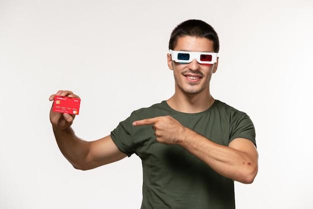 Vorderansicht junger mann im grünen t-shirt, das bankkarte in d sonnenbrille auf weißen wandfilm einsamen kinofilmen hält