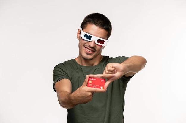 Vorderansicht junger mann im grünen t-shirt, das bankkarte in der d sonnenbrille hält, die auf einsamen kinofilmen des weißen wandfilms lächelt