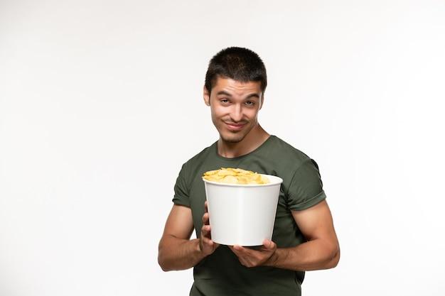Vorderansicht junger mann im grünen t-shirt, das kartoffelspitzen auf dem einsamen filmfilmkino der weißen schreibtischperson hält