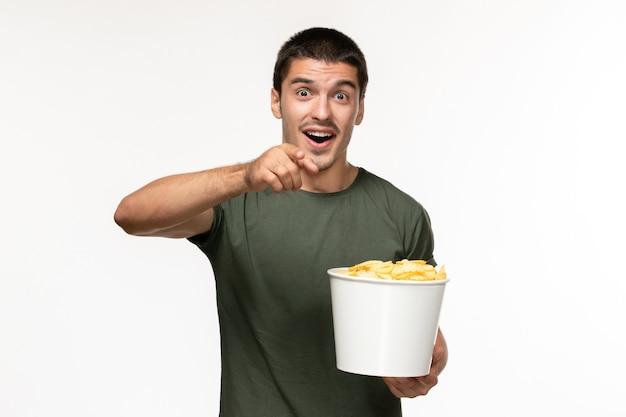 Vorderansicht junger mann im grünen t-shirt, das kartoffelspitzen hält und film auf einsamen filmkino der hellen weißen wand sieht