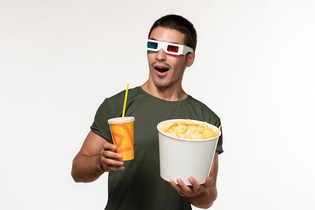 Vorderansicht junger mann im grünen t-shirt, das kartoffelspitzen-soda in -d sonnenbrille auf weißem einsamem film des weißen wandfilms hält