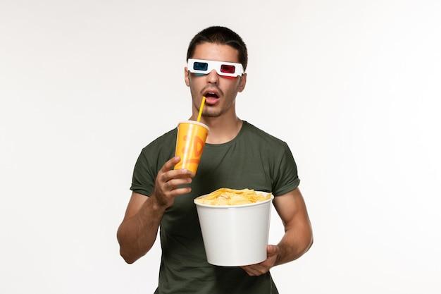 Vorderansicht junger mann im grünen t-shirt, das kartoffelspitzen-soda in d sonnenbrille auf weißem einsamen filmkino des weißen schreibtischfilms hält