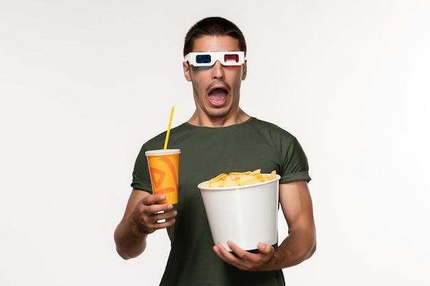 Vorderansicht junger mann im grünen t-shirt, das kartoffelspitzen-soda in -d sonnenbrille auf weißen wandfilm-männlichen einsamen filmen hält