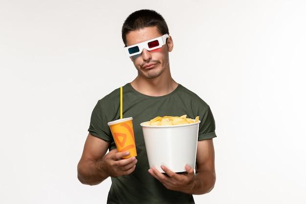 Vorderansicht junger mann im grünen t-shirt, das kartoffelspitzen und soda in der d sonnenbrille auf weißem einsamen film des weißen schreibtischfilms hält