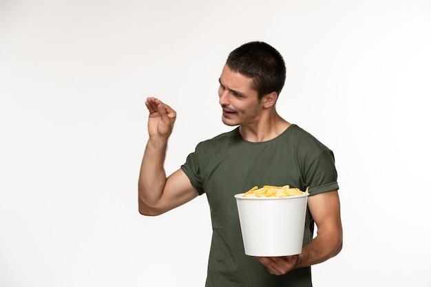 Vorderansicht junger mann im grünen t-shirt, das korb mit cips auf weißem filmfilm des einsamen filmkinos des weißen wandfilms hält