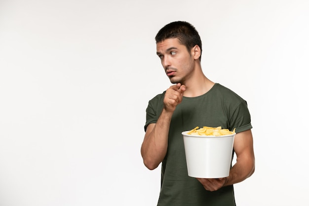 Vorderansicht junger mann im grünen t-shirt, das korb mit cips auf weißem filmkino der einsamen filmkino-person der weißen wand hält
