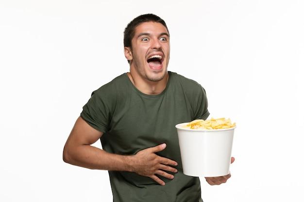 Vorderansicht junger mann im grünen t-shirt, das korb mit kartoffelspitzen hält, die film auf einsamem filmfilmkino der weißen wand ansehen