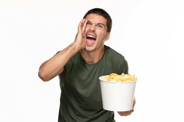 Vorderansicht junger mann im grünen t-shirt, das korb mit kartoffelspitzen hält und auf weißem wand-filmkino des einsamen genusses schreit