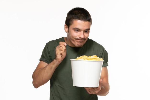 Vorderansicht junger mann im grünen t-shirt, das korb mit kartoffelspitzen hält und sie auf weißem wand-film des einsamen genussfilmfilms der weißen wand isst