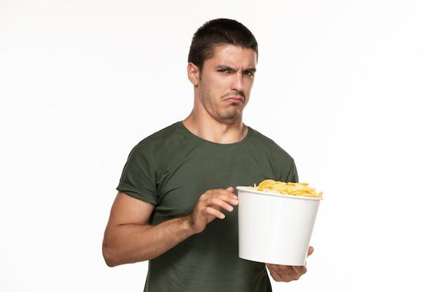 Vorderansicht junger mann im grünen t-shirt, das korb mit kartoffelspitzen hält und sie auf weißem wand-filmkino des einsamen genusses isst