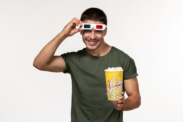 Vorderansicht junger mann im grünen t-shirt, das popcorn hält und in d sonnenbrille auf weißen wandfilm einsamen kino-männerfilmen abhebt