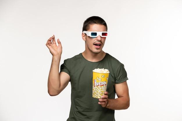 Vorderansicht junger mann im grünen t-shirt, das popcorn in d sonnenbrille auf dem weißen schreibtischfilm einsamer kino-männerfilm hält