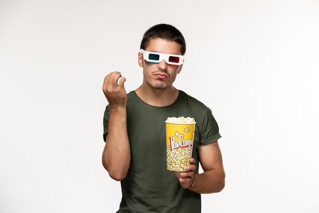 Vorderansicht junger mann im grünen t-shirt, das popcorn in d sonnenbrille auf weißem wandfilm einsamen kino-männerfilm hält