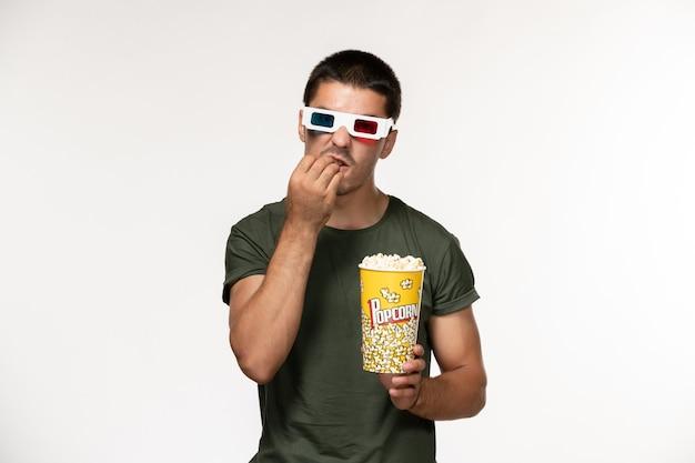 Vorderansicht junger mann im grünen t-shirt, das popcorn in d sonnenbrille auf weißen wandfilm einsamen kino-männerfilmen hält